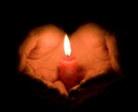 geloof hoop liefde: Handen cupped rond een brandende kaars