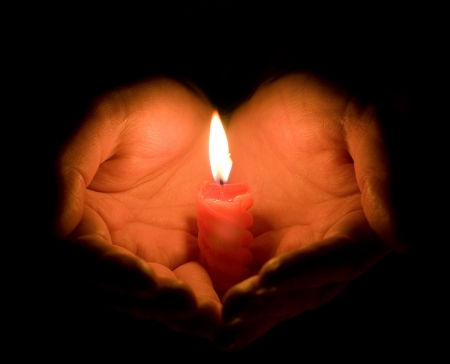 Hands cupped around a burning candle photo