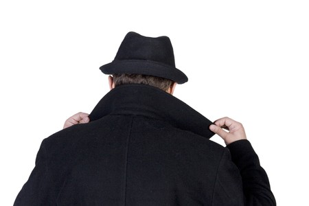 spies: Mysterious man wearing a black hat and a black coat with a raised collar Stock Photo