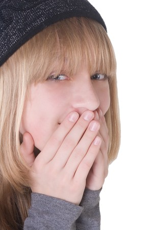 Laughing blonde teenage girl covering her mouth with her hands (with focus on hands and mouth)