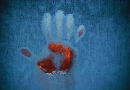 Slightly blurred bloody handprint on a frozen window (symbolizing horror or fear) photo