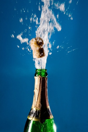 Bottle of champagne with a popping cork (against a blue background) photo
