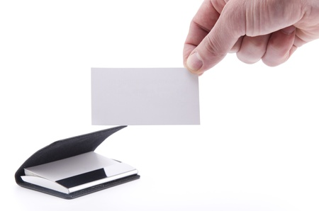 holder: Hand holding a blank paper card (isolated on white), with a pile of paper cards in the business card holder in the background Stock Photo