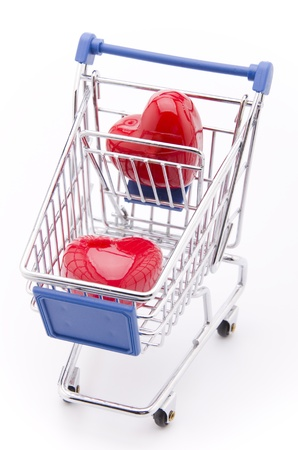Love for Sale (a shopping cart with two bright red hearts isolated on white) Stock Photo - 9430919
