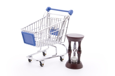 Time for Shopping (a shopping cart and an hour-glass isolated on white) Stock Photo - 9430913