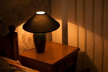 Cozy lamp on a night stand near a bed (shining in the darkness) Stock Photo