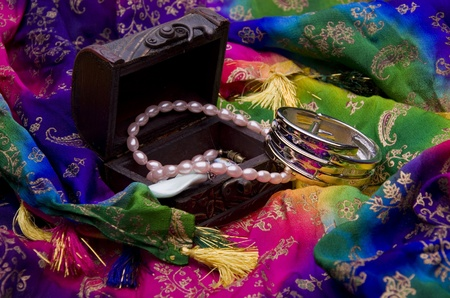 Ancient treasure chest with jewelry on a multi-colored oriental fabric background photo