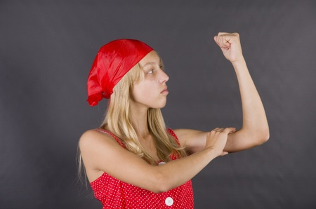 Young girl posing like Rosie the Riveter in a classic World War II poster (We Can Do It)