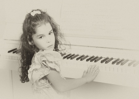 Beautiful little girl near a white piano (in sepia, vintage style) photo
