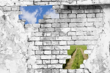 break: Old brick wall in black and white  with blue sky and lane across a green field showing through the holes