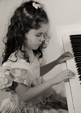 Beautiful little girl near a white piano  in sepia, vintage style  photo