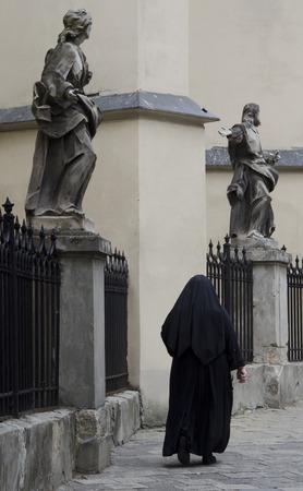 nun: Catholic nun walking down a street past medieval statues