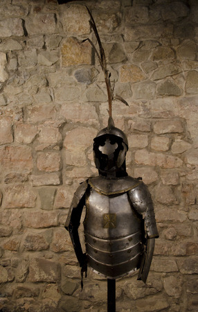 crusade: Medieval knight armor in a vault (against the background of a brick wall) Stock Photo