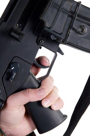 gatillo: Mano que sostiene un arma con el dedo en el gatillo aislado en blanco