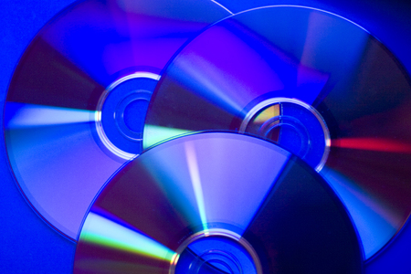 cd rom: Slightly blurred compact discs in dark blue tones as an abstract technological background