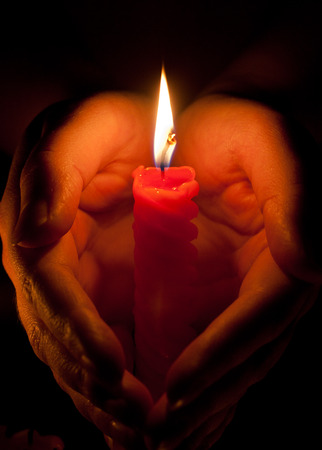 cupped: Hands cupped around a burning candle