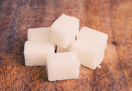 surface aged: Sugar cubes on an aged wooden surface (retro style) Stock Photo