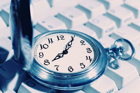 timekeeping: Ancient pocket watch on the computer keyboard (retro style)