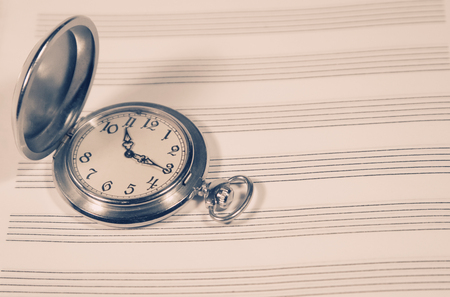 timekeeping: Pocket watch on a sheet of music paper (retro style, with copy space)