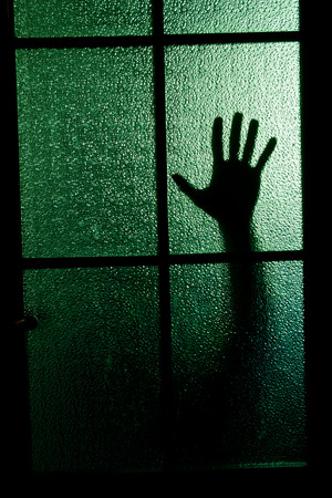 Blurred silhouette of a hand behind a window or glass door Stock Photo