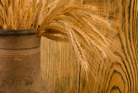 crock: Old crock with a bunch of wheat ears against the background of a wooden wall