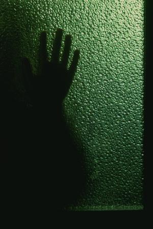 penetracion: silueta borrosa de una mano detrás de una ventana o puerta de vidrio