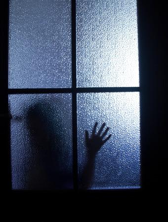 Wazig silhouet van een kind achter een glazen deur in het donker (in blauw tinten)