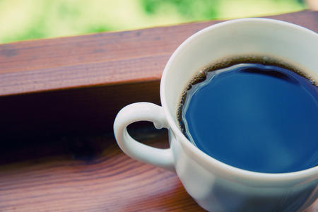 sky reflection: White coffee cup with freshly made coffee on a window sill, retro style, selective focus (with the blue sky reflected in coffee)