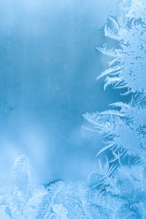 Slightly blurred beautiful frost pattern on a window glass (with copy space for your text), abstract winter background Stock Photo