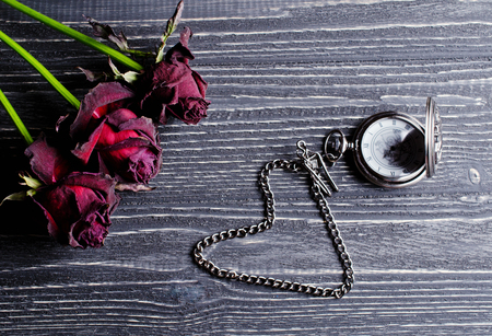 Three beautiful dry roses and an antique pocket watch with a heart-shaped chain against an aged wooden background (retro toned, vintage style)