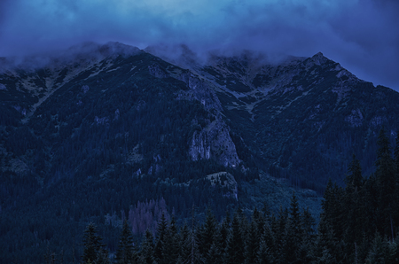 Blurred silhouettes of spooky foggy mountains and woods at night (in dark blue tones)