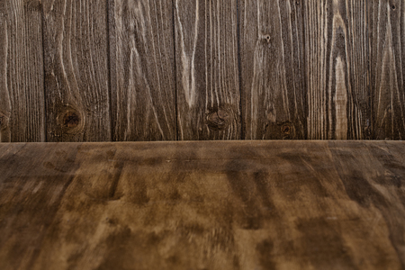 Dark grungy wooden texture as a forefront and grungy wooden boards as a background (selective focus on the wooden boards)