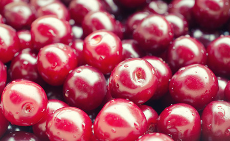 Macro shot of cherries with drops of water as a bright red fruit background (selective focus), retro style Stock Photo