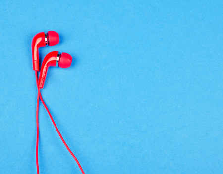 Bright red earbud headphones isolated on a bright blue background with copy space on the right for your text (minimal concept, top view)