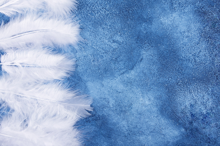 Fluffy white feathers on a blue marble or concrete background (as an abstract fairy-like fantastic background), copy space on the right for your text