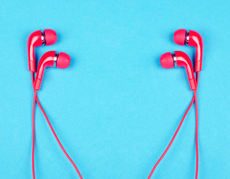 Two pairs of bright red earbud headphones isolated on a bright blue background (minimal concept, top view), copy space in the center for your text Stock Photo