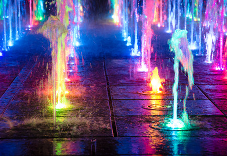 Beautiful multicolored dancing fountains at night (as a colorful abstract background)