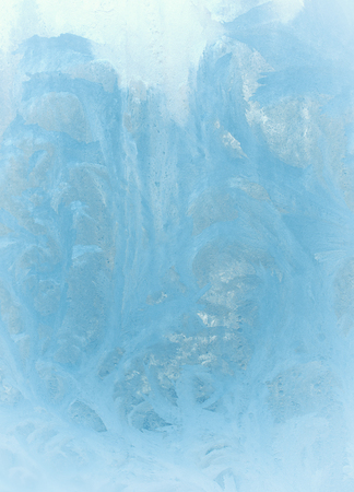 Fantastic fairy-like light blue frost pattern on the window glass (as an abstract winter background), retro toned Stock Photo
