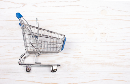 Shopping cart on a white wooden background (sale concept), top view, copy space on the right for your text