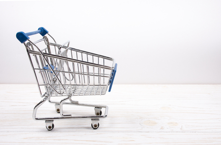 Shopping cart on a white wooden background (sale concept), copy space on the right for your text Stock Photo