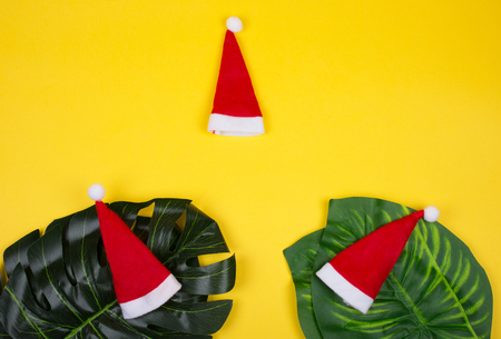 Three small Santa hats and tropical leaves on the bright yellow background as the tropical Christmas concept (copy space in the center for your text) Stockfoto - 112880895