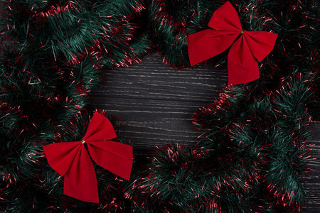 Two bright red Christmas bows and green and red tinsel forming a frame on a black wooden background as a New Year or Christmas background (top view, copy space in the center for your text)