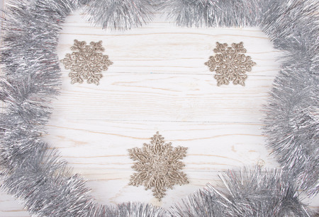 Snowflakes as Christmas decorations and silver tinsel forming a frame on a white wooden background (top view, copy space in the center for your text)