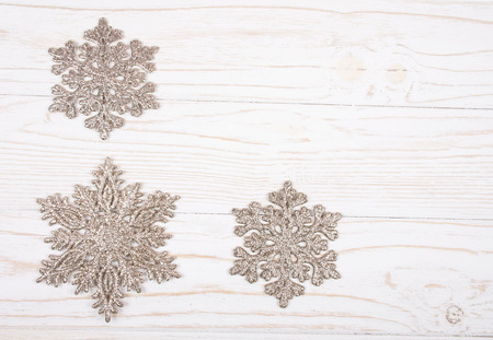 Snowflakes as Christmas decorations on a white wooden background (top view, copy space for your text)