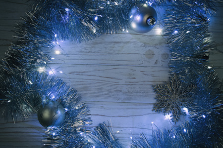 Garland with Christmas lights and Christmas decorations on a wooden background at night as the New Year or Christmas background in blue tones (selective focus), copy space in the center for your text