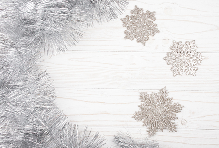 Silver tinsel and snowflakes forming a frame on a white wooden background (top view, copy space in the center for your text) Stock Photo