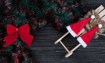 Two Santa hats on a toy Christmas sleigh, Christmas bow and green and red tinsel on a black wooden background as a New Year or Christmas background (top view, copy space for your text) Stockfoto - 112880918