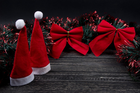 Two Santa hats, two red Christmas bows and green and red tinsel on a black wooden background as a New Year or Christmas composition (copy space for your text, selective focus on Santa hats)