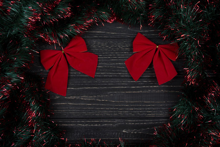 Two bright red Christmas bows and green and red tinsel forming a frame on a black wooden background as a New Year or Christmas background (top view, copy space for your text)