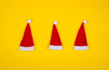 Three small Santa hats on the bright yellow background as the Christmas concept (top view, minimal style)